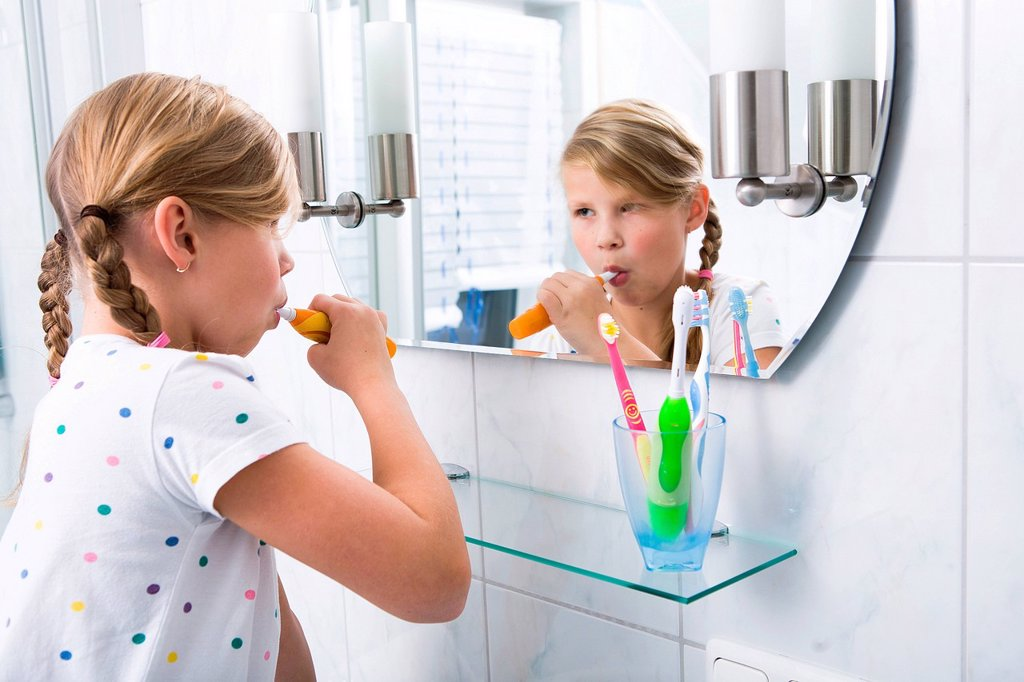 Little girl brushing her teeth in the bathroom : Stock Photo