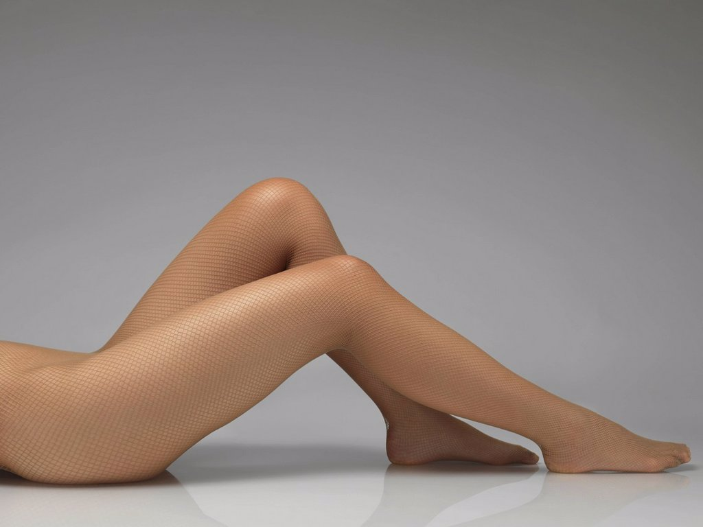 Woman´s legs in beige fishnet pantyhose : Stock Photo