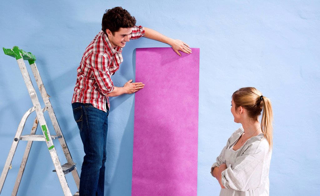 Young couple applying wallpaper to a wall : Stock Photo