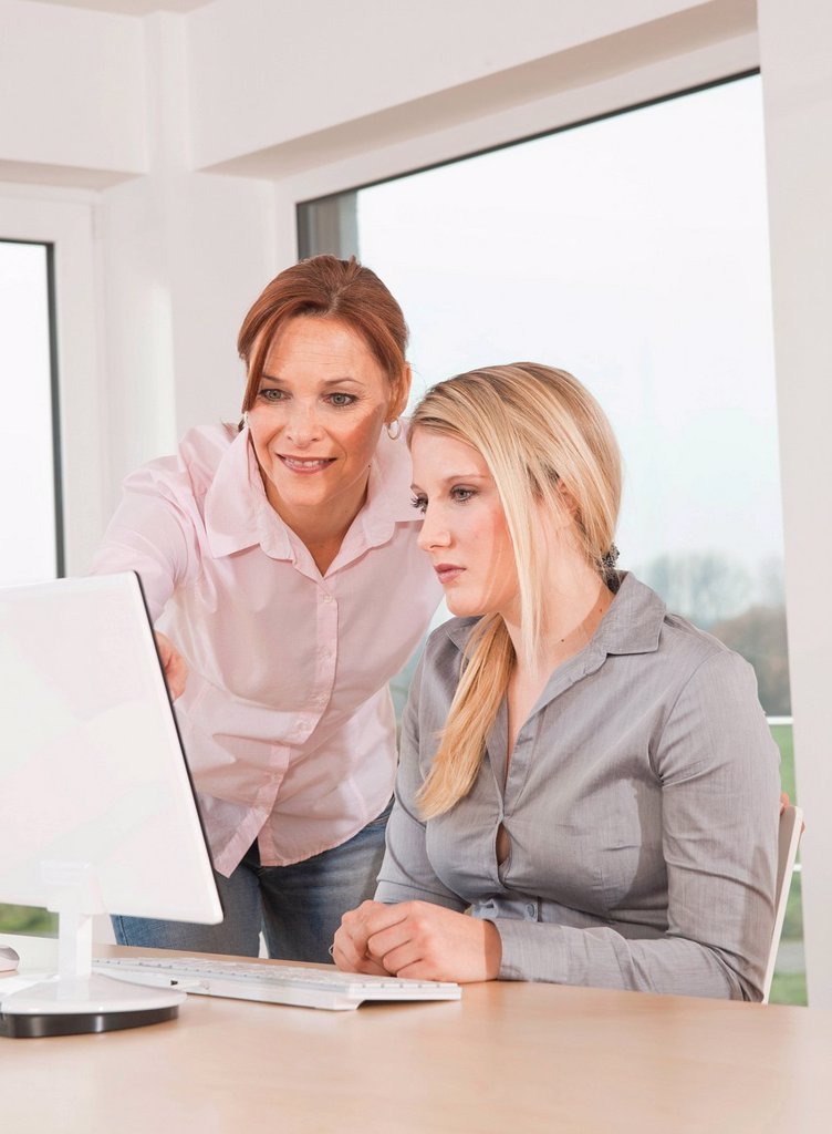 Stock Photo: 1848R-634391 Two women working together on a computer