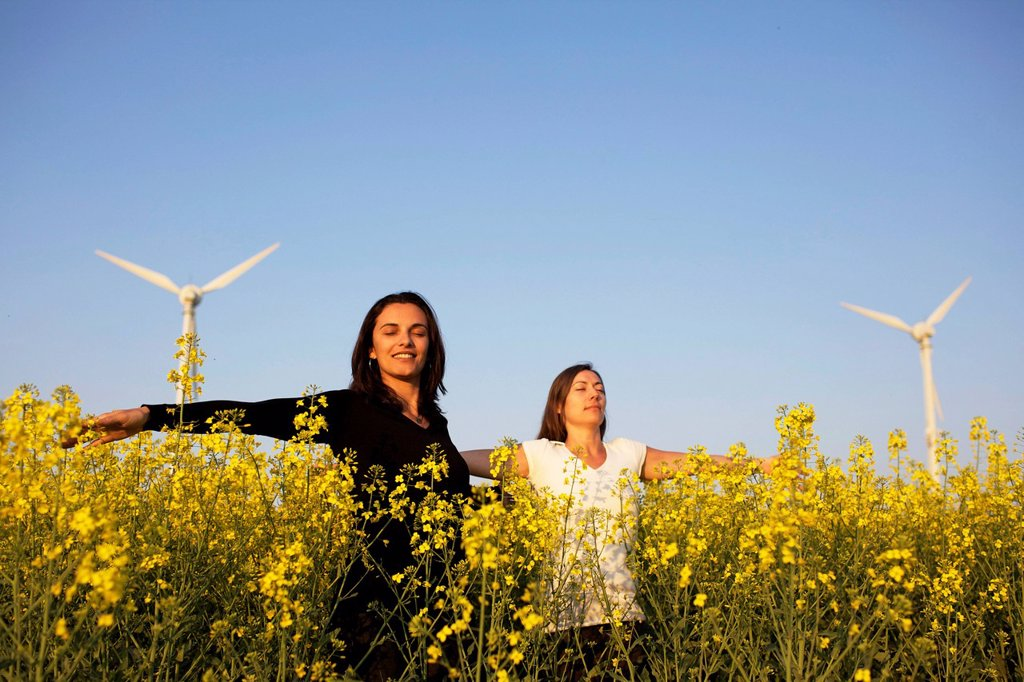 Two women in a canola field in front of a wind turbine : Stock Photo