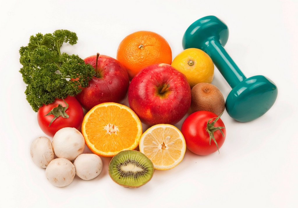 Fruit and vegetables with a dumbbell : Stock Photo