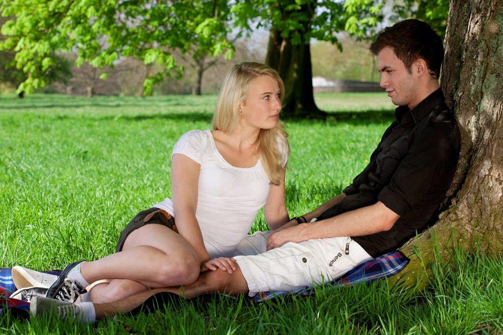 Young couple sitting on a picnic blanket and leaning against a tree in a park in spring : Stock Photo