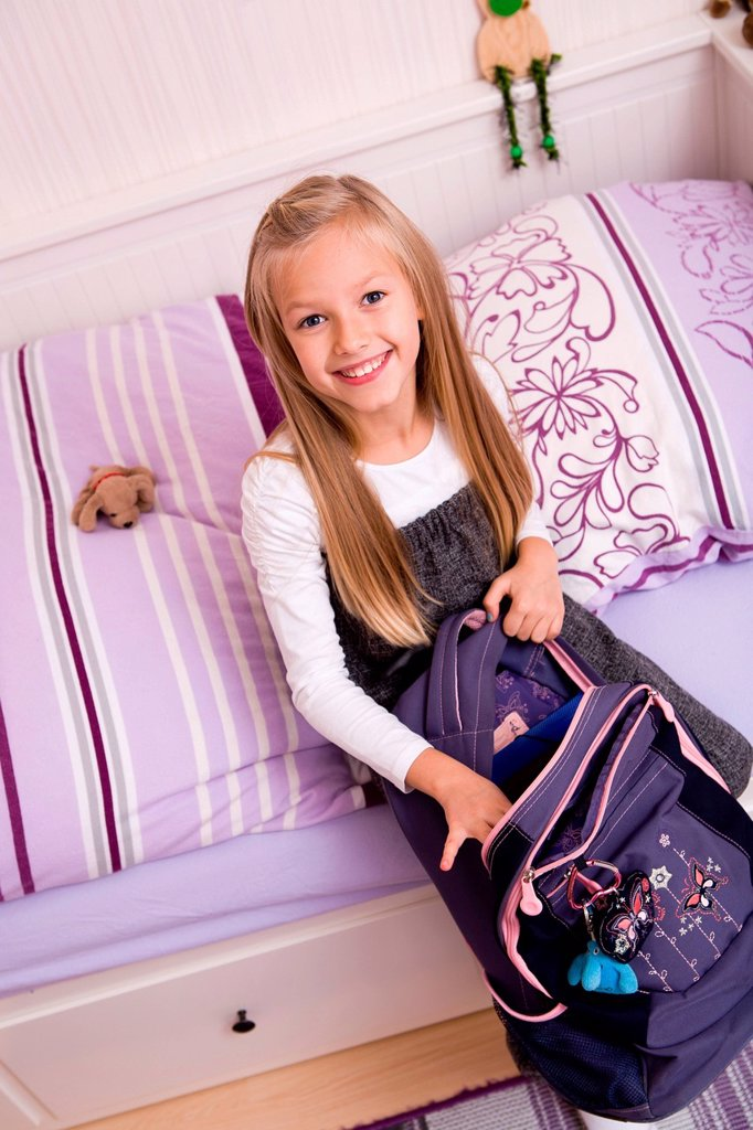 Stock Photo: 1848R-635217 Girl, 9, packing her backpack for school