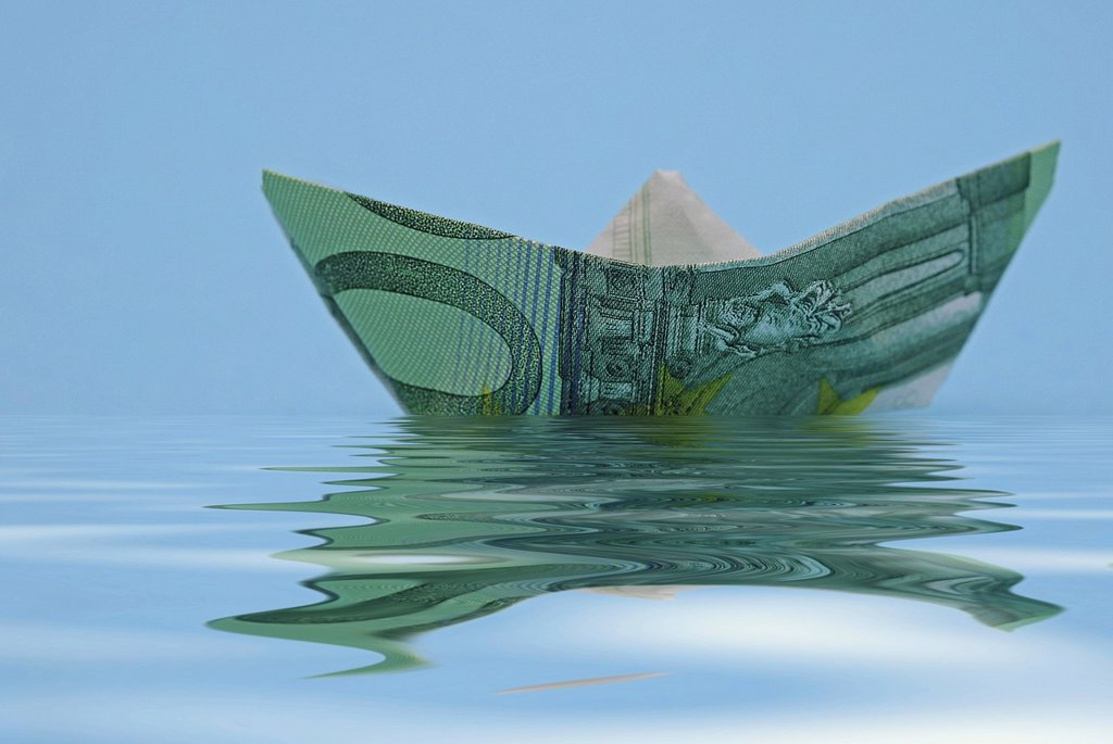 Paper boat folded from a euro banknote, symbolic image for a ship cruise or vacation pay : Stock Photo