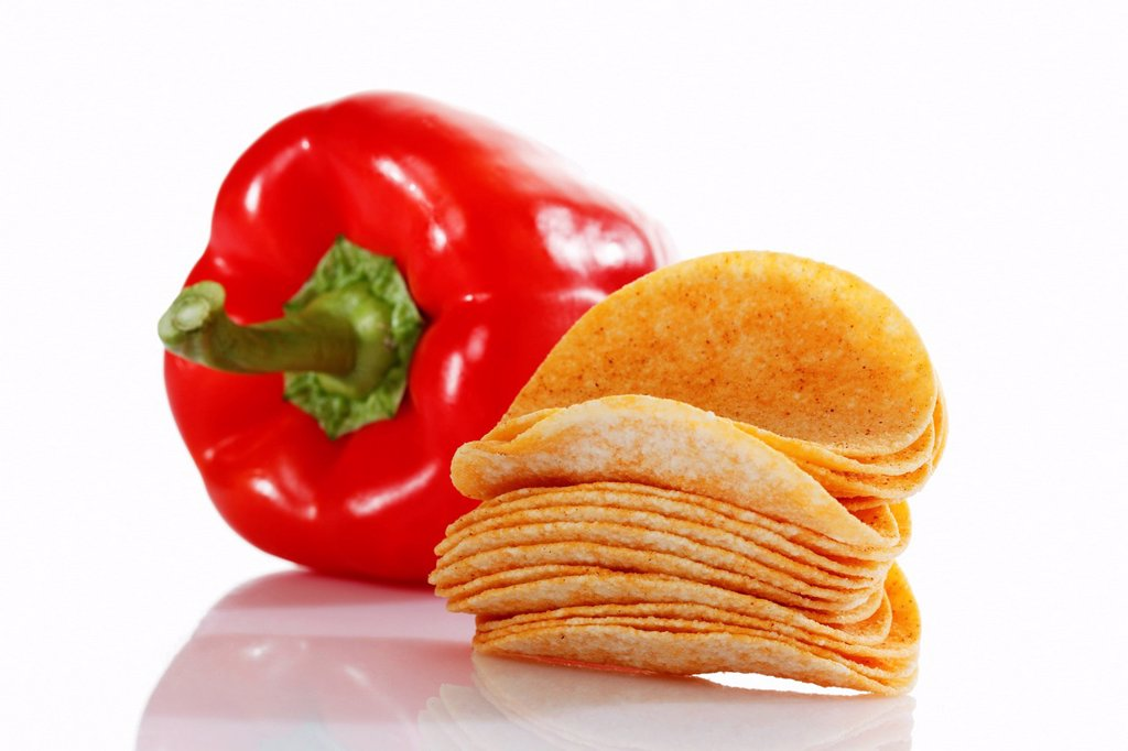 Oval paprika potato chips, stacking chips, stacked beside a capsicum : Stock Photo