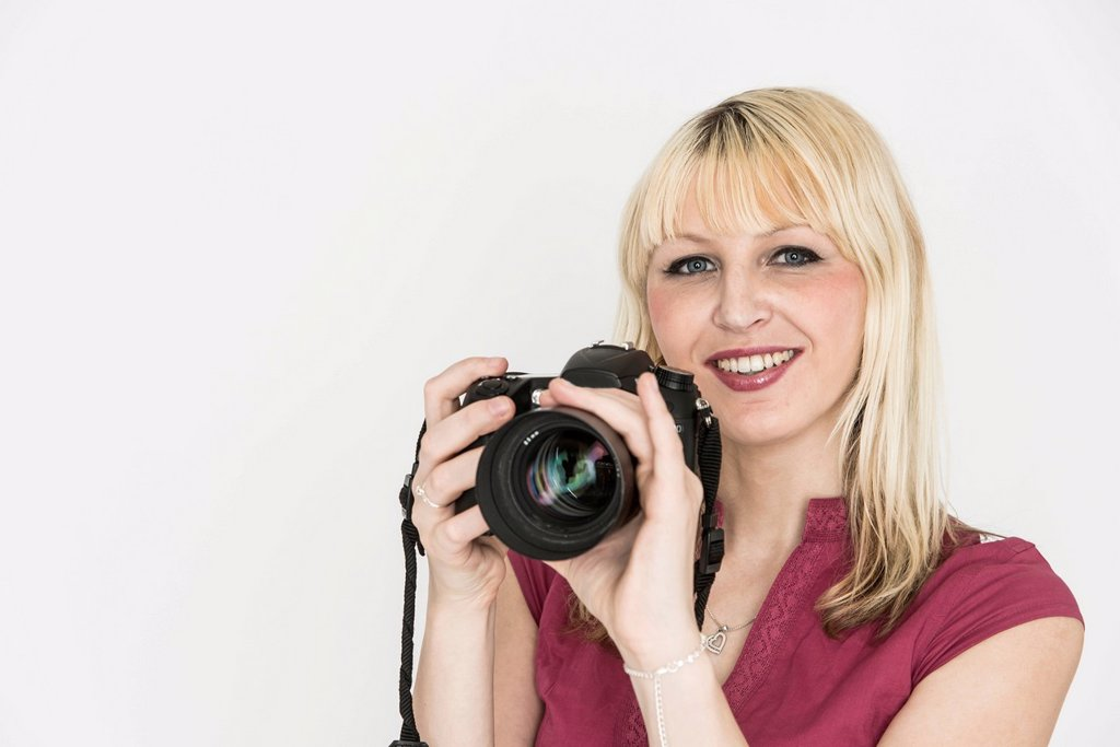 Young woman holding a SLR camera : Stock Photo