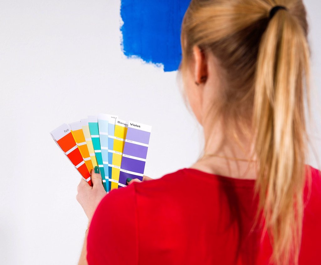 Stock Photo: 1848R-637252 Young woman holding colour cards in front of a wall