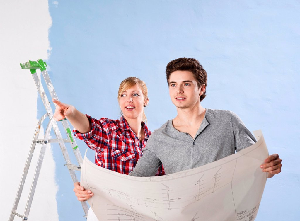 Stock Photo: 1848R-637257 Young couple looking at a plan