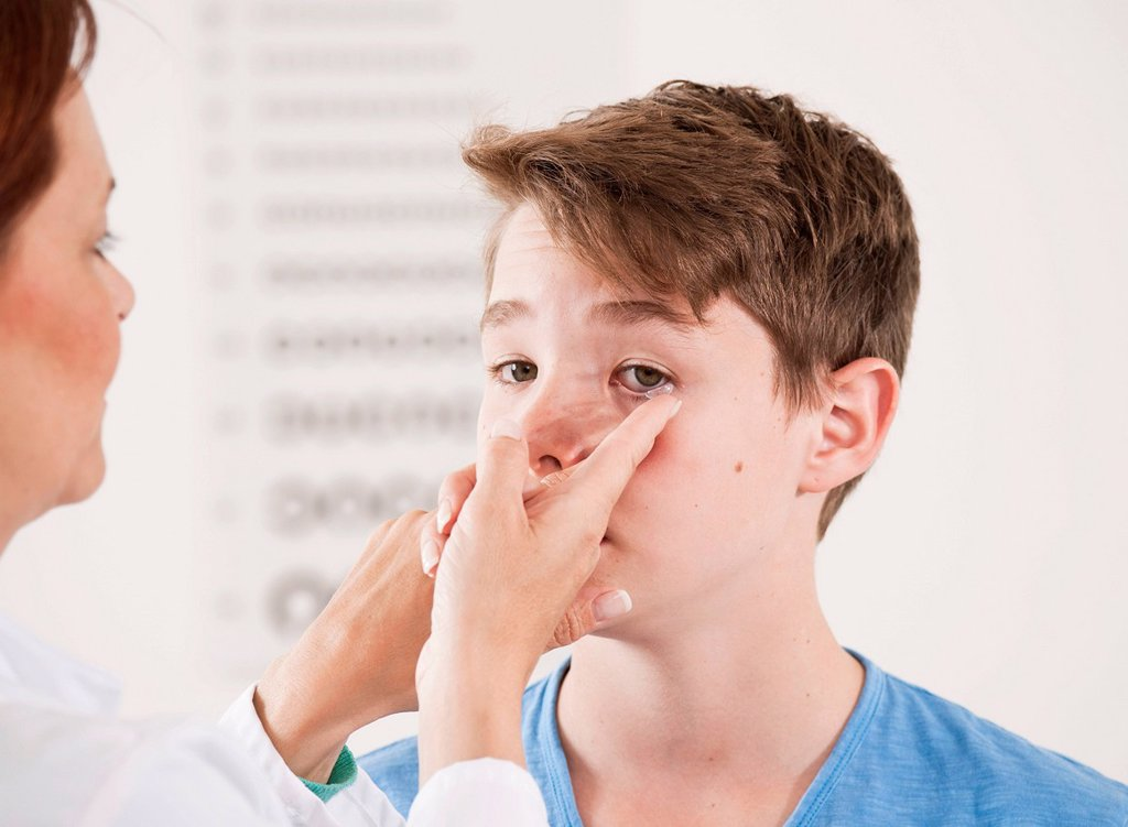 Stock Photo: 1848R-637582 Ophthalmologist explaining the use of contact lenses to a teenage boy