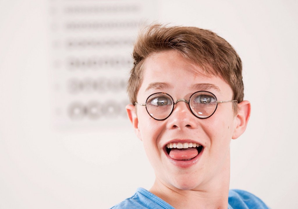 Stock Photo: 1848R-638230 Teenage boy, portrait wearing thick_glassed glasses in front of a sight test