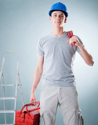 Young craftsman holding a tool box : Stock Photo