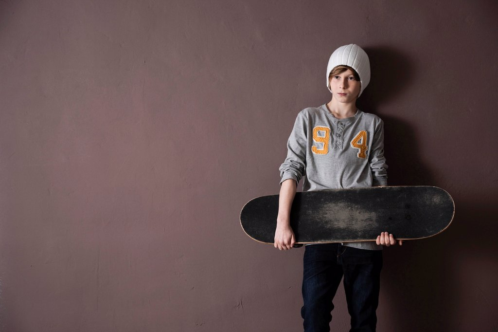 Cool boy wearing a cap and holding a skateboard : Stock Photo