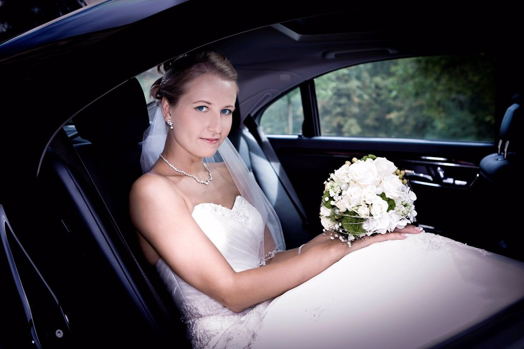 Young bride in a car : Stock Photo