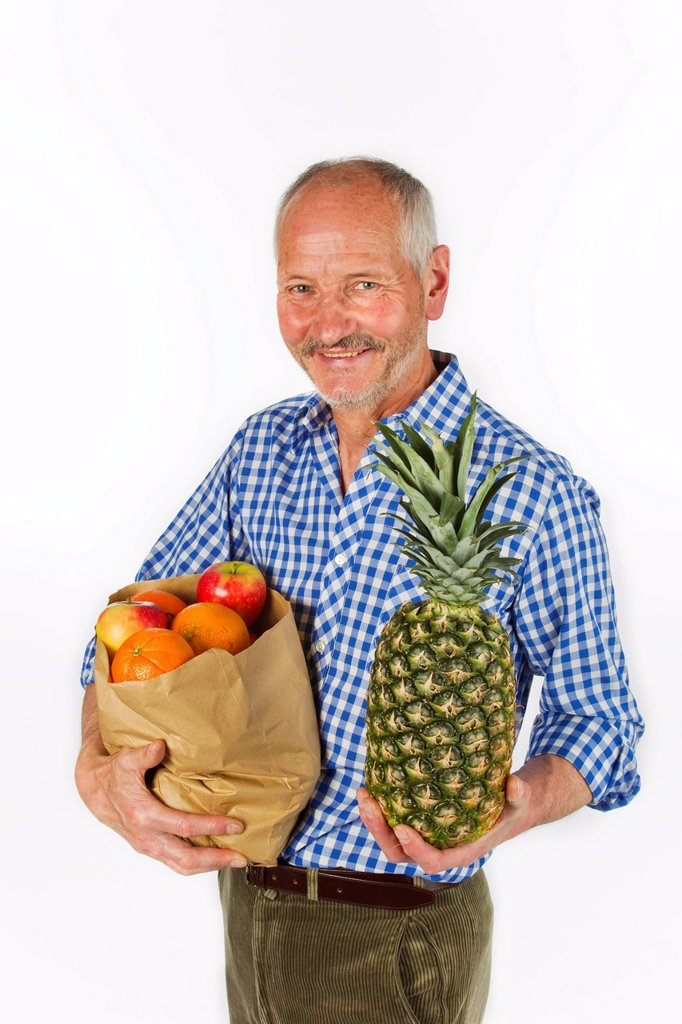 Stock Photo: 1848R-639960 Elderly man with a bag of fruit and a pineapple in his hand