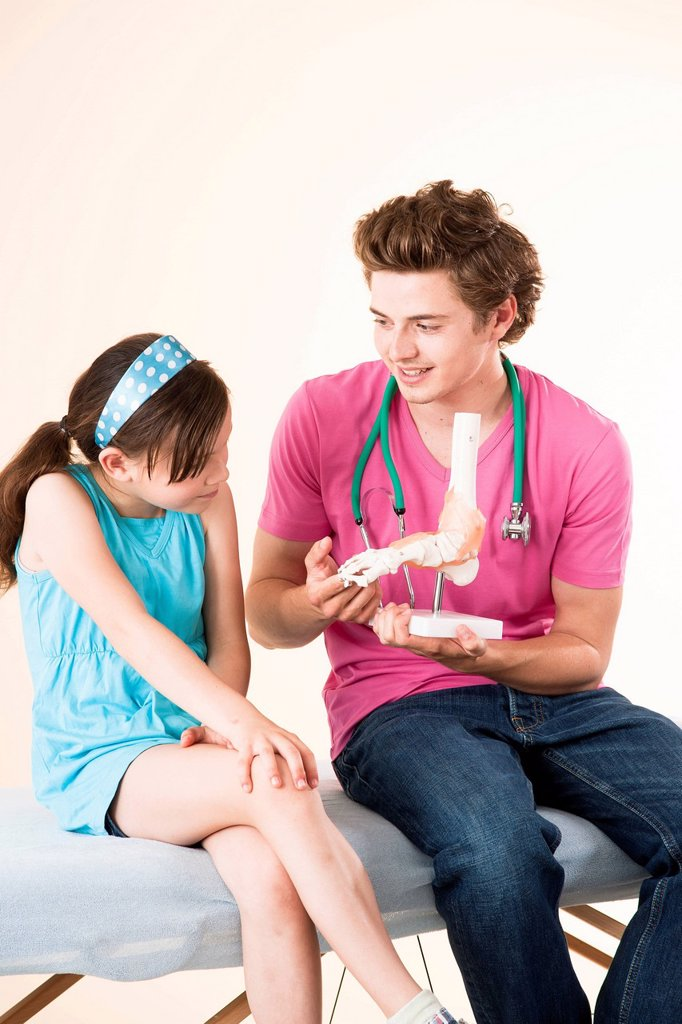Doctor explaining a model of a foot to a girl : Stock Photo