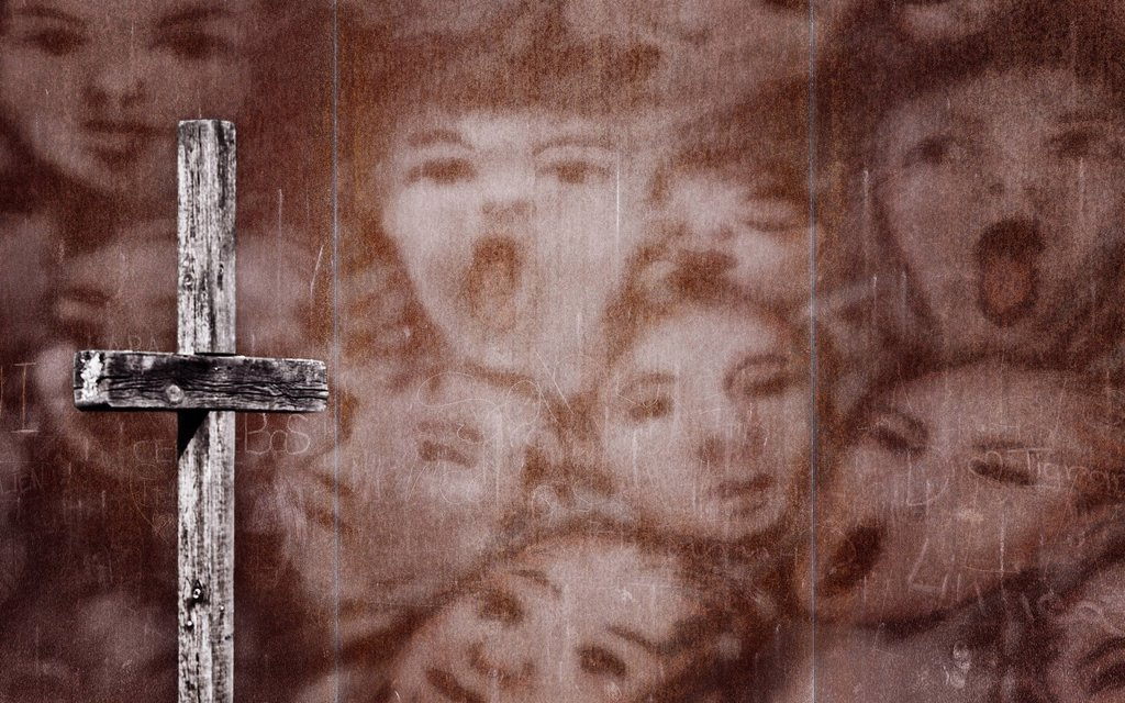 Wooden cross in front of a rusty wall with a drawing of screaming people, photomontage : Stock Photo