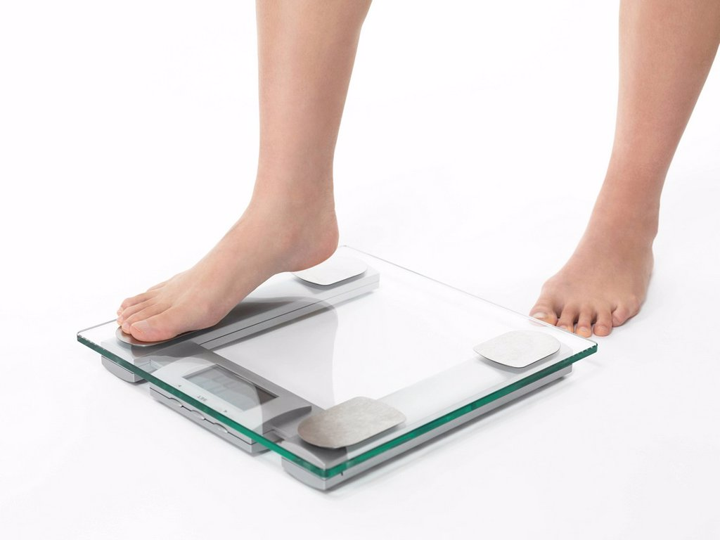 Stock Photo: 1848R-641598 Woman´s legs stepping on scales