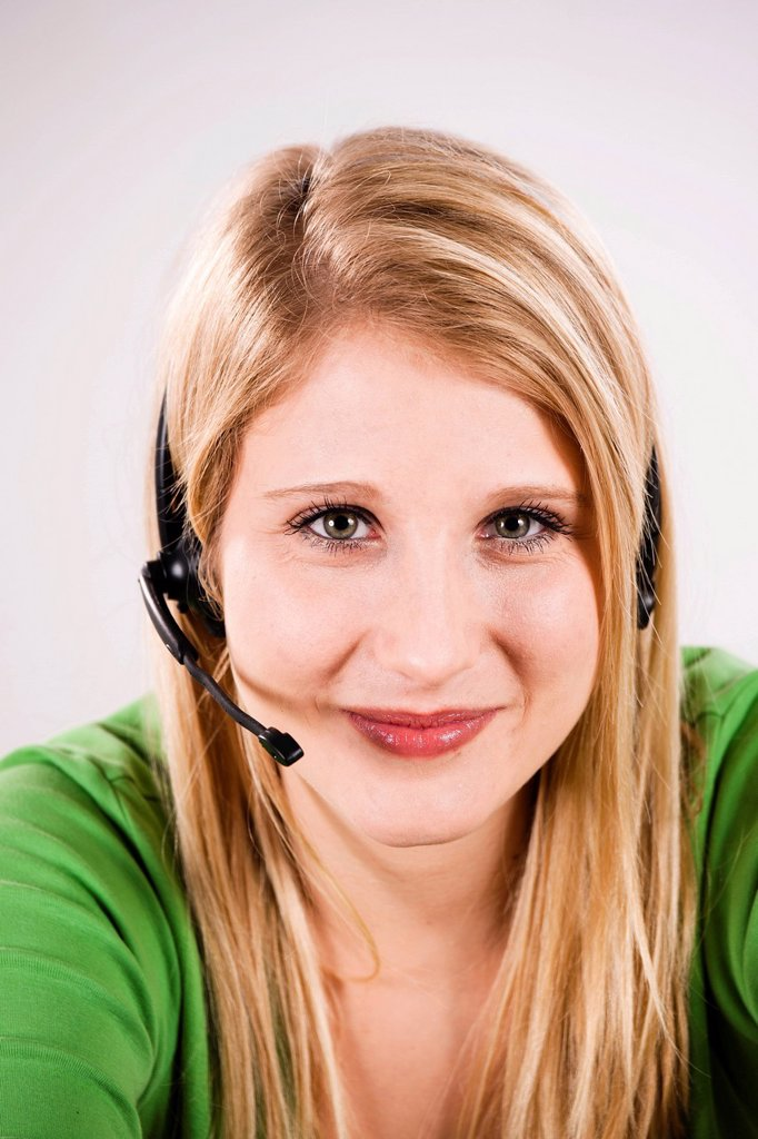 Smiling young woman with a headset, portrait : Stock Photo