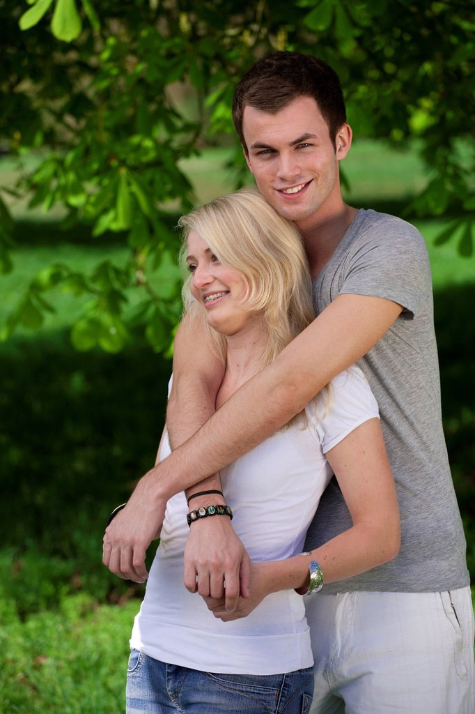 Young man embracing a young woman in a park in spring : Stock Photo
