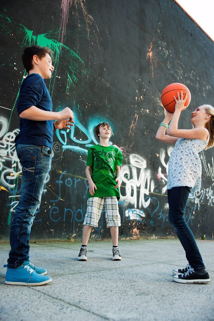 Three friends playing basketball in front of a graffiti wall : Stock Photo