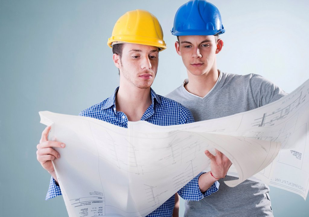 Stock Photo: 1848R-644668 Two young tradesmen looking at a building plan