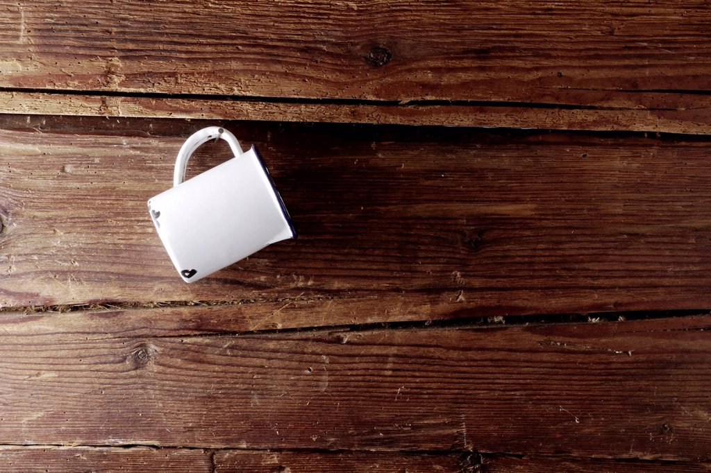 Stock Photo: 1848R-645246 Old enamel cup hanging on a rustic wooden wall