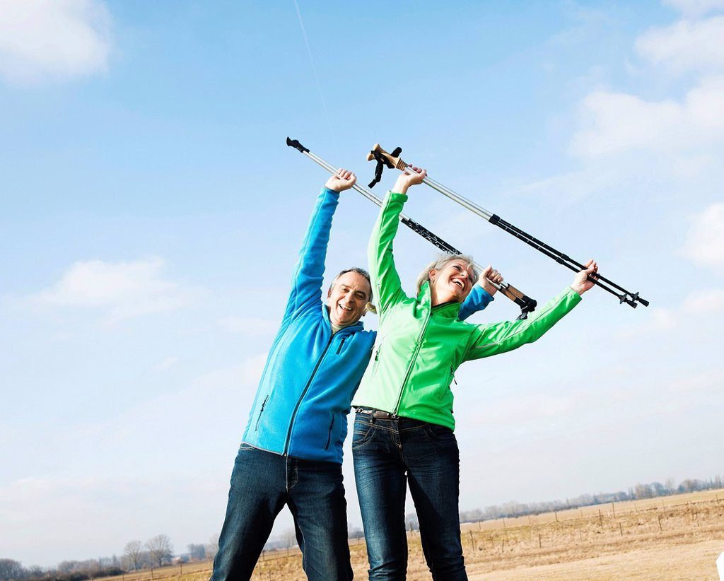 Stock Photo: 1848R-646134 Senior couple doing exercises with walking sticks in a field