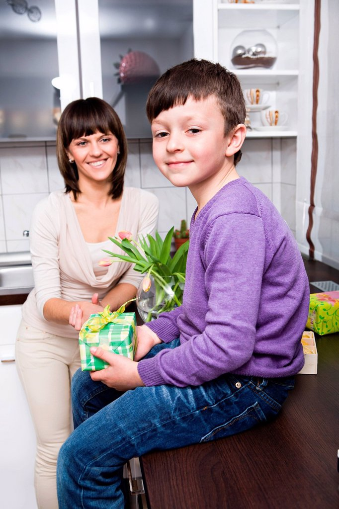 Stock Photo: 1848R-646146 Young woman and her son in the kitchen, with Easter presents