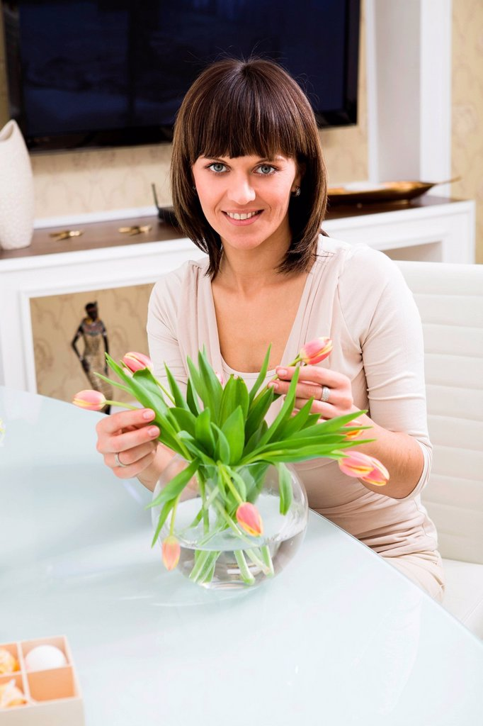 Young woman with a bunch of tulips at home : Stock Photo