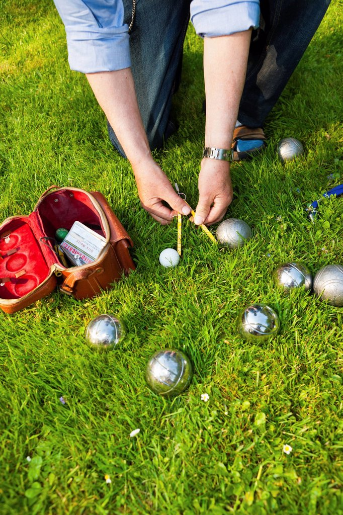 Stock Photo: 1848R-734471 Man playing boules, petanque, measuring the distances between the balls, Hesse, Germany, Europe