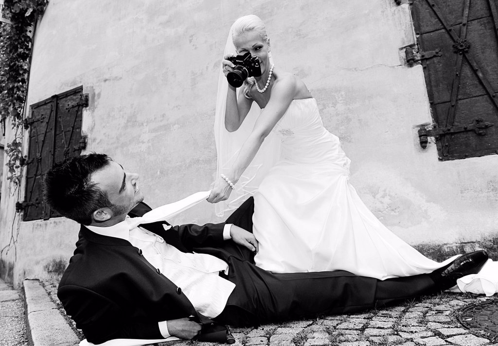 Bride photographing the groom with an old camera, photo shoot, wedding : Stock Photo