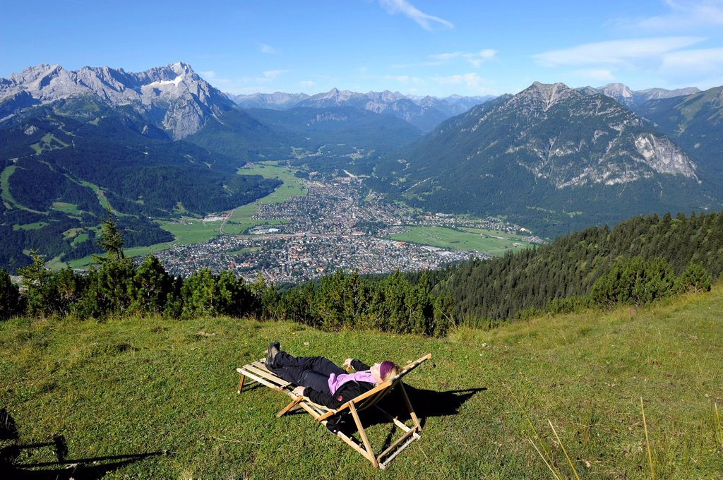 Stock Photo: 1848R-736114 Young woman in a deck chair, view of Garmisch_Partenkirchen, Zugspitze mountain, Jubilaeumsgrat ridge and Alpspitze mountain as seen from Wank mountain, Upper Bavaria, Bavaria, Germany, Europe