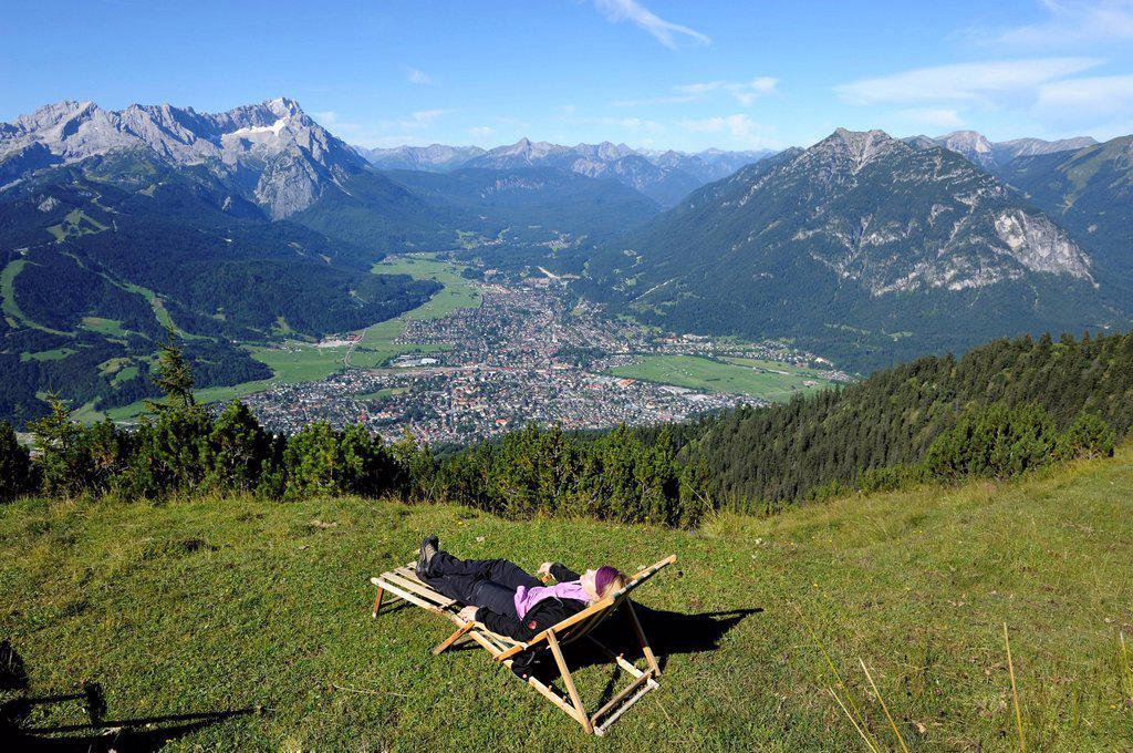 Young woman in a deck chair, view of Garmisch_Partenkirchen, Zugspitze mountain, Jubilaeumsgrat ridge and Alpspitze mountain as seen from Wank mountain, Upper Bavaria, Bavaria, Germany, Europe : Stock Photo