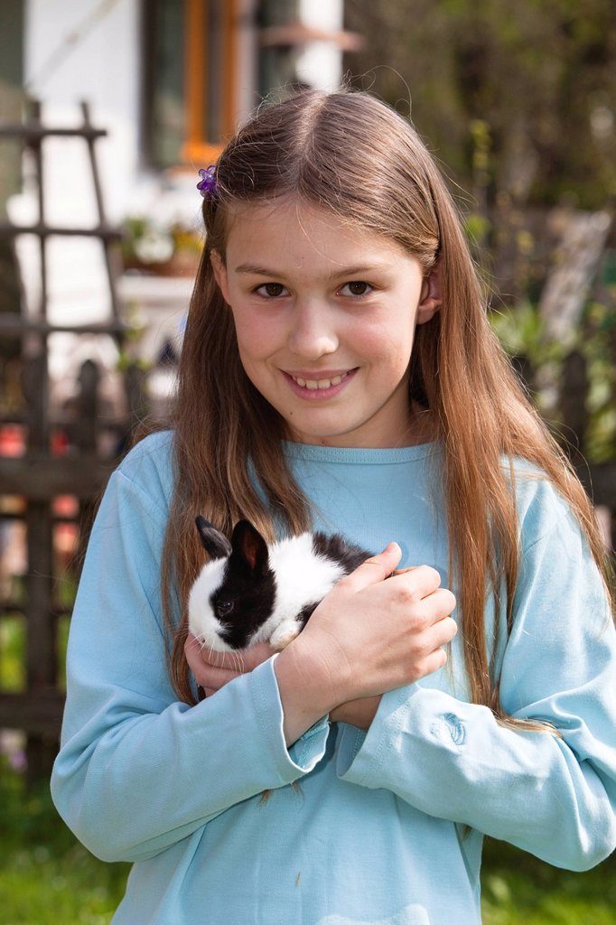 Stock Photo: 1848R-737204 Girl, 10 years old, with pet rabbit