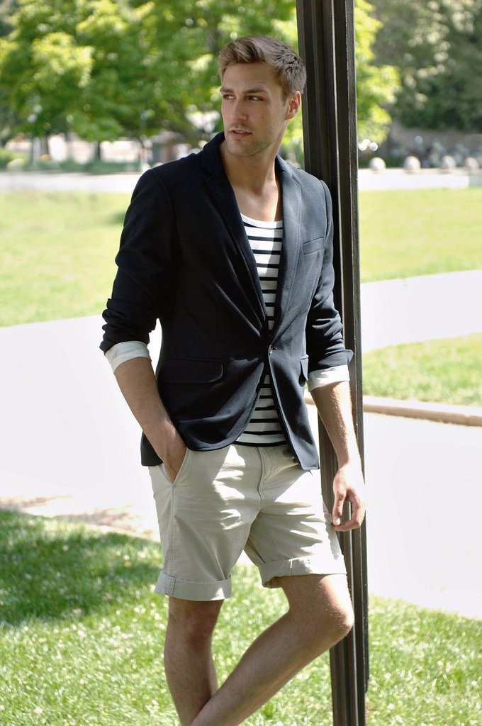 Stock Photo: 1848R-737523 Young man in casual outfit leaning on a lamppost in a summerly park