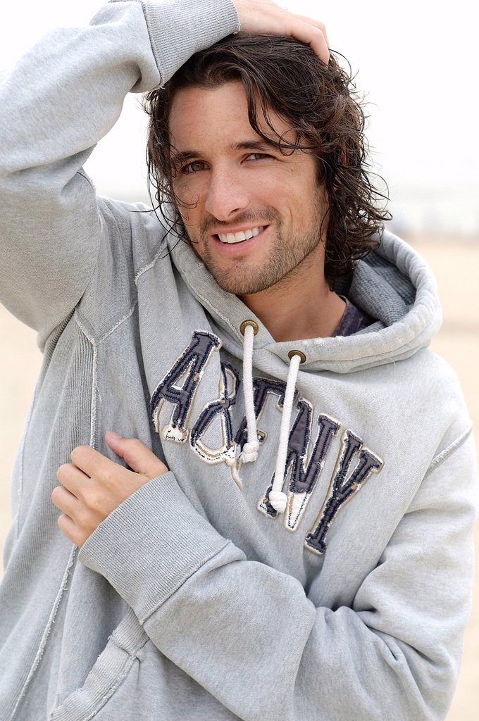 Man, early 30s, wearing a hooded sweater in bad weather at the beach : Stock Photo