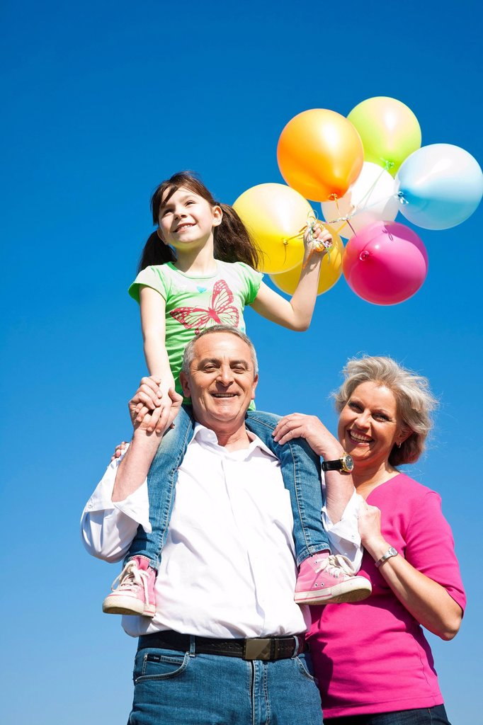 Grandparents holding their granddaughter while she is holding coloured balloons in her hand : Stock Photo