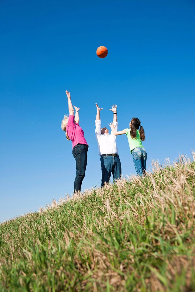 Girl playing ball with her grandparents on a meadow : Stock Photo