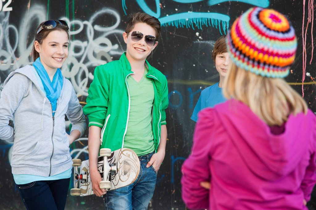 Teenagers standing in front of a wall with graffiti : Stock Photo