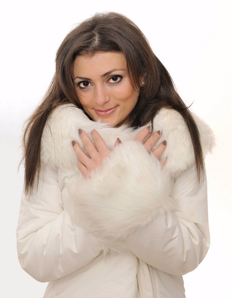 Young woman in a white faux fur coat : Stock Photo