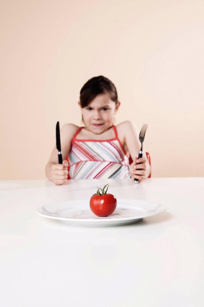 Girl holding a knife and a fork looking disgustedly at a tomato : Stock Photo