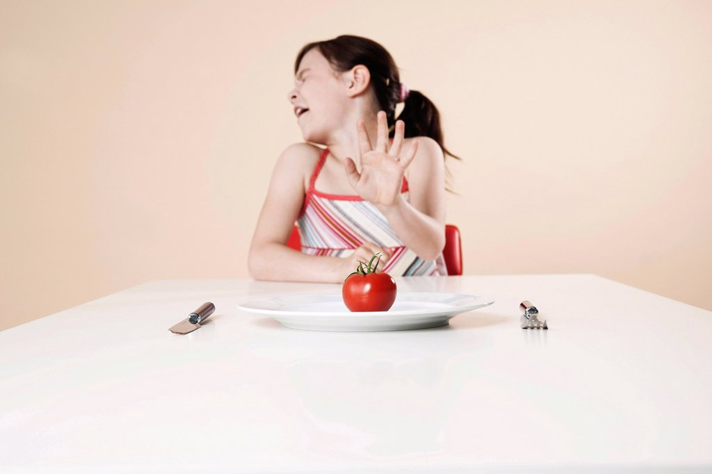 Girl turns away in disgust from a tomato : Stock Photo