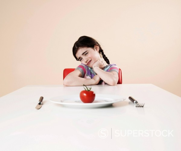 Stock Photo: 1848R-740308 Girl looking with disgust at the tomato on her plate
