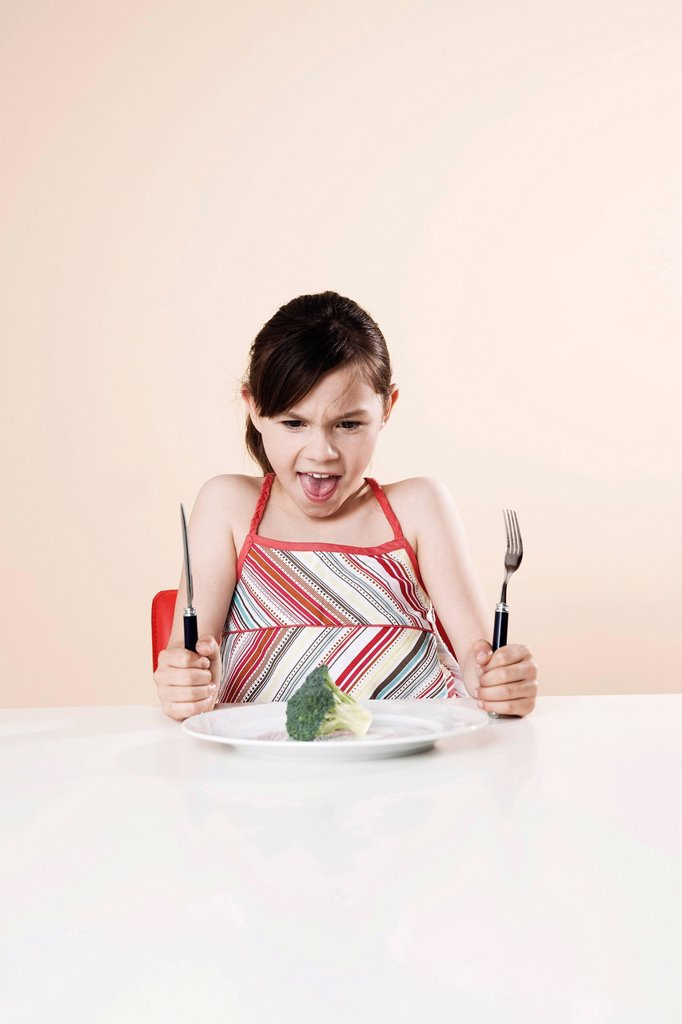 Girl holding a knife and a fork looking disgustedly at a piece of broccoli : Stock Photo