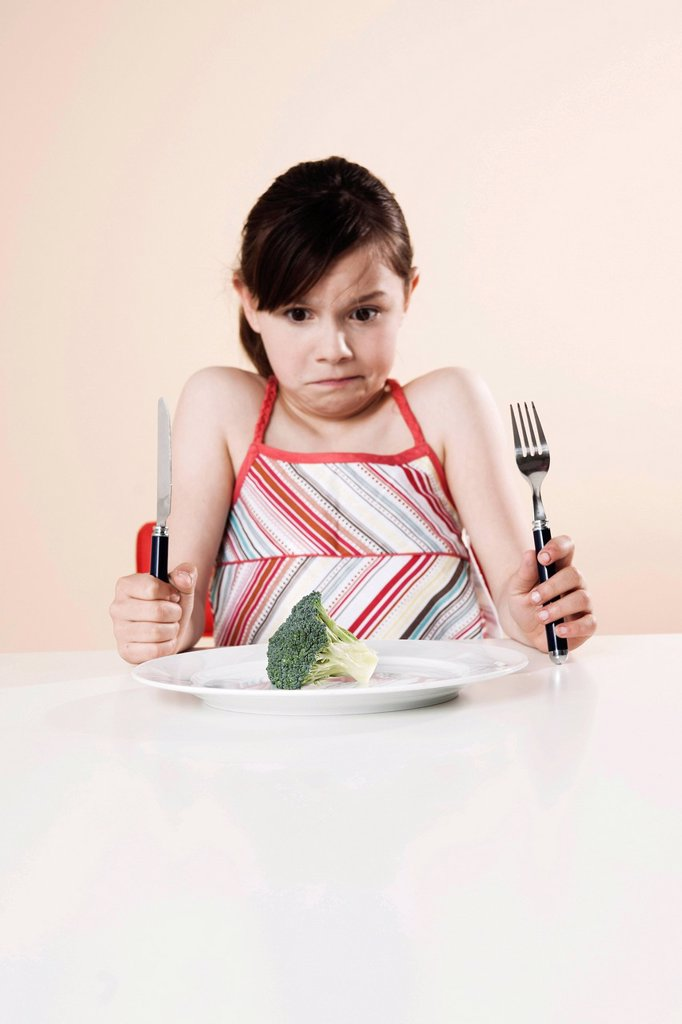 Stock Photo: 1848R-740312 Girl holding a knife and a fork looking disgustedly at a piece of broccoli