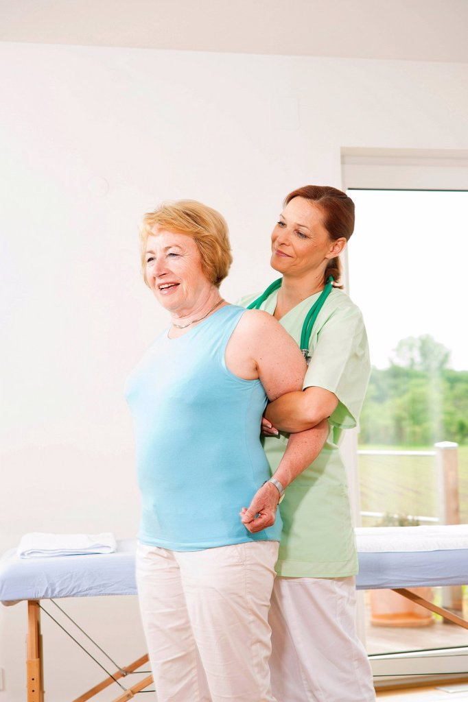 Woman being treated on her shoulder by a physiotherapist : Stock Photo