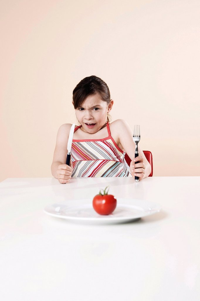 Stock Photo: 1848R-740547 Girl holding a knife and a fork looking disgustedly at a tomato