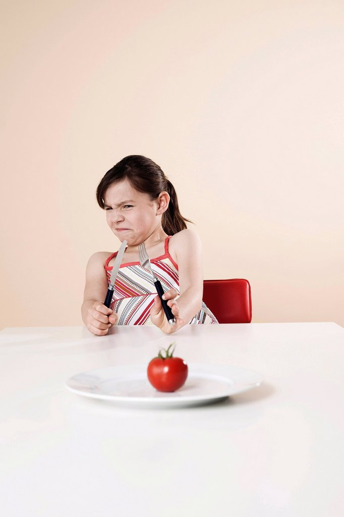 Stock Photo: 1848R-740548 Girl holding a knife and a fork looking disgustedly at a tomato