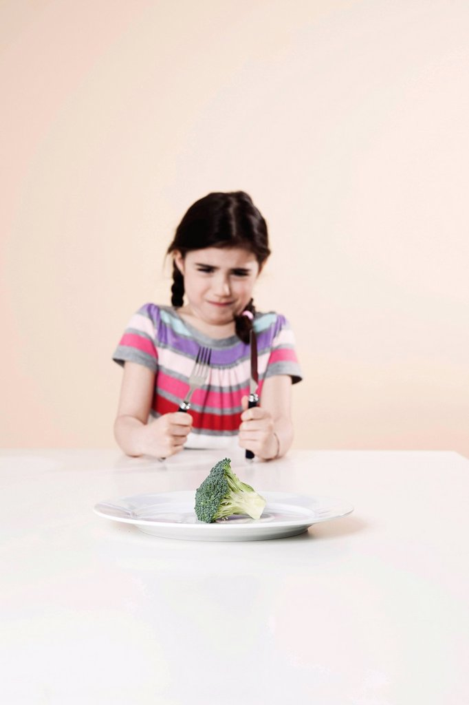 Girl looking with disgust at the broccoli on her plate : Stock Photo